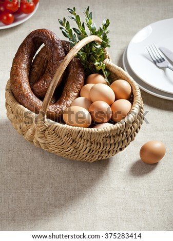 Easter basket with smoked sausage, eggs and twig of box tree - stock photo