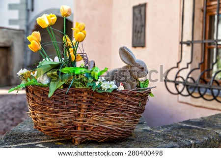 Easter basket with yellow flowers and baby bunny, outdoor - stock photo