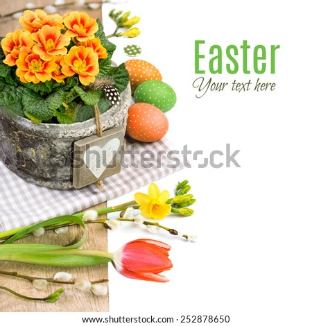 Easter border with primrose, spring flowers and natural decorations on white background, space for your text - stock photo