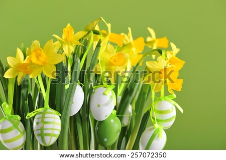 Easter bouquet with narcissus and hanging easter eggs - stock photo