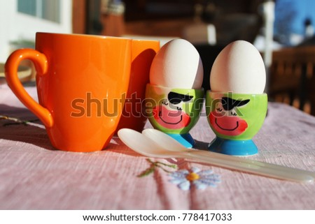 Easter breakfast on the balcony in spring with funny egg cups
