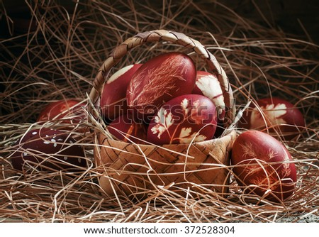 Easter brown egg with a pattern of grasses, dyed in onion skins in a wicker basket in straw, the Orthodox Christian tradition, selective focus - stock photo