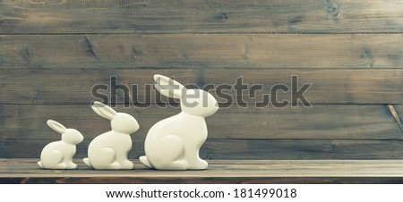 easter bunnies over rustic wooden background. retro style toned picture - stock photo