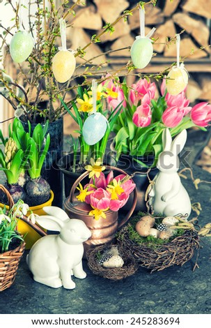 Easter bunny and eggs decoration. Spring flowers tulips, snowdrops and narcissus blooms. Retro style toned picture. Selective focus - stock photo