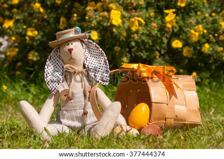Easter bunny and eggs in wicker on green grass. Happy Easter greeting card