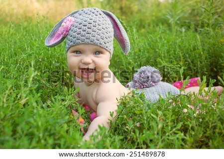 Easter bunny baby in green grass. Happy childhood outdoors. - stock photo