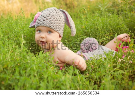Easter bunny baby in green grass meadow.  - stock photo