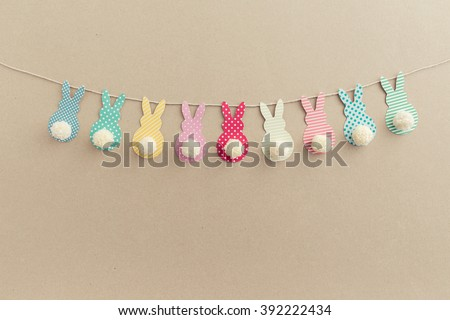Easter Bunny Banner. Cute bunny shapes with yarn pom pom tails. - stock photo