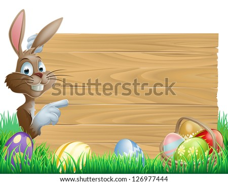 Easter bunny character pointing at a blank sign with space for text. Surrounded by painted chocolate eggs