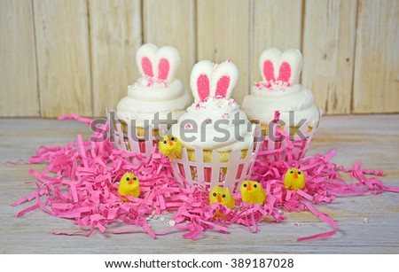 Easter bunny ears in cupcake icing with baby chicks in pink grass - stock photo