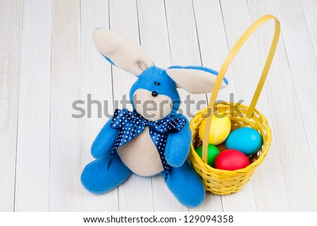 Easter bunny, eggs in basket on table - stock photo