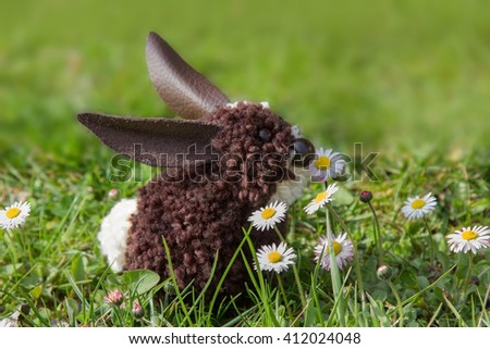 easter bunny, made of pompoms, sitting in the lawn with daisies. self-made handicraft. - stock photo