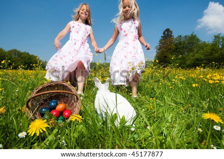 Easter bunny on a beautiful spring meadow with dandelions in front of a basket with Easter eggs; children in the background coming on an Egg hunt - stock photo