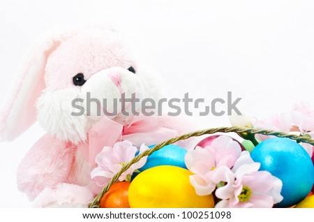Easter bunny toy with the basket with flowers and color eggs, isolated on a pink background - stock photo