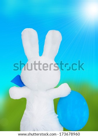 Easter Bunny with Easter Egg on blue sky background - stock photo