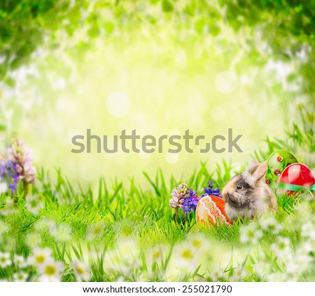 Easter bunny with eggs and flowers in grass over green garden tree leaves background - stock photo