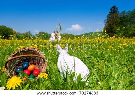 Easter bunny with eggs on a meadow in spring, two children in the background - stock photo