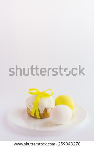 Easter cake and easter eggs on the plate on a white background. Selective focus - stock photo