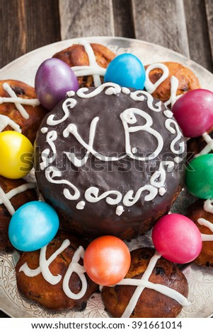 Easter cake, hot cross buns and colored eggs on plate - stock photo