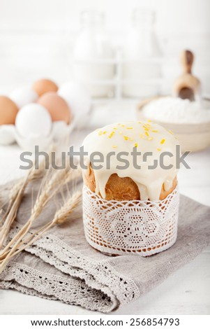 Easter cake, kulich with glaze, eggs on a white wooden background/ traditional Russian pastry.