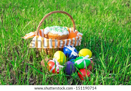 Easter cake on a striped napkin in a basket and eggs on green spring grass