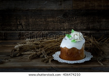 Easter cake on wooden background with wheat.