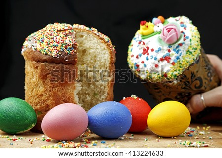 Easter cake with colored eggs on a black background on a wooden Board