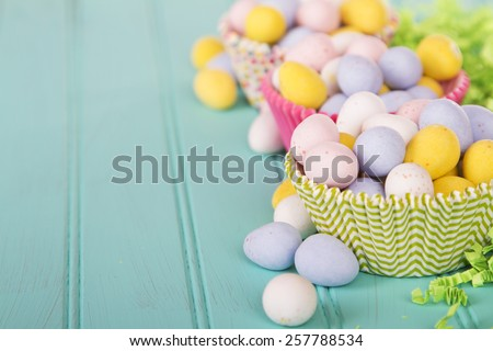 Easter Candy in cup cake wrappers on a turquoise blue wood panel - stock photo