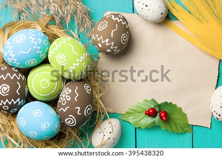 Easter card. Painted Easter eggs with piece of paper for congratulation on a natural blue wooden background