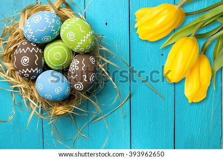 Easter card with colorful eggs in nest and yellow tulips over blue background. Top view with copy space - stock photo