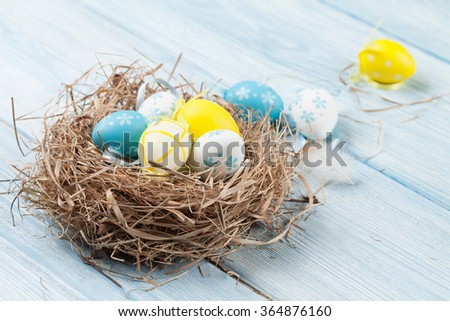 Easter card with colorful eggs in nest over wooden table. Top view with copy space - stock photo
