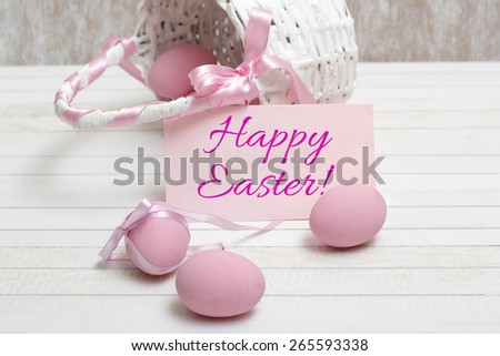 Easter Card with Message Happy Easter on the letter ,composition with white basket and pink eggs on wooden table  - stock photo