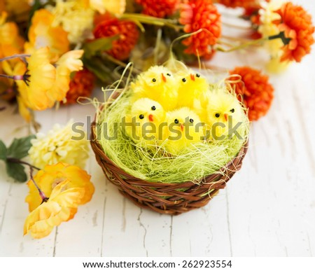 Easter Chickens in a Nest with Colorful Flowers in the Background  - stock photo