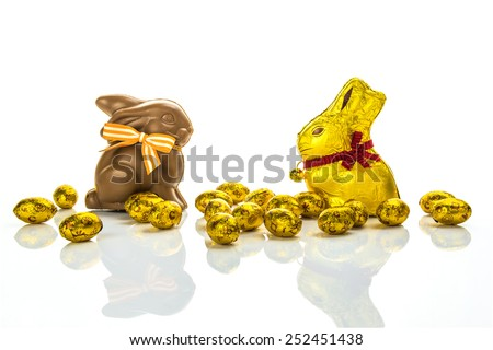 Easter chocolate bunnies and golden eggs on white background - stock photo