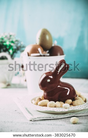 Easter. Chocolate  Eggs and bunny on Easter table. Tulips in vase. Easter setting  on table - stock photo