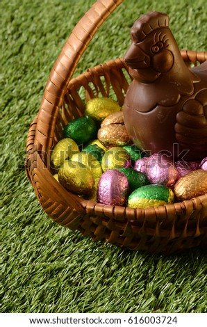 Easter chocolate eggs and chicken, hen on green grass