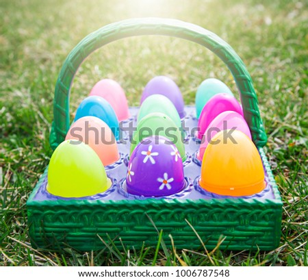 Easter colorful egg in basket on green grass outside