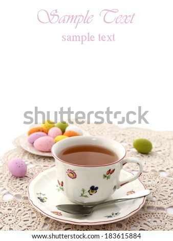 easter composition of tea cup and easter eggs on white - stock photo