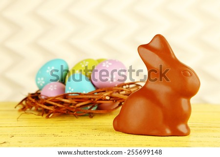 Easter composition with chocolate rabbit on light background - stock photo