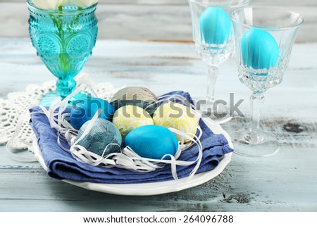 Easter composition with colorful eggs on napkin on wooden table background - stock photo