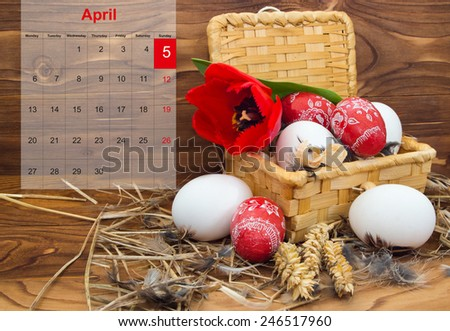 Easter composition with eggs and flower tulip in a basket with a calendar for April 2015 on the wooden background - stock photo