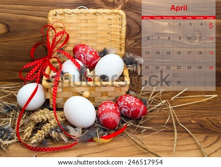 Easter composition with eggs  in a basket with a calendar for April 2015 on the wooden background - stock photo