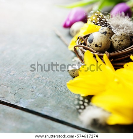 Easter composition with tulips, colorful eggs and nest on rustic background