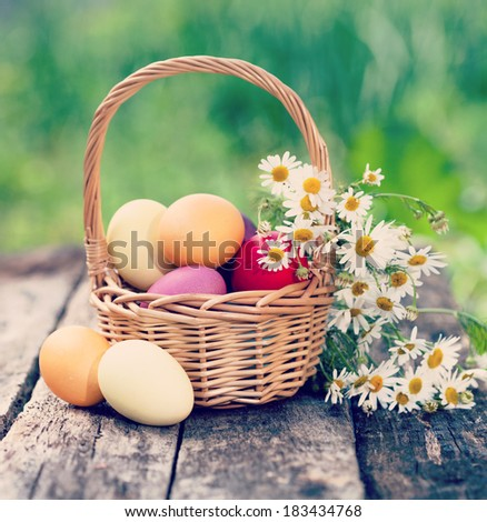 Easter concept - eggs, basket and daisies. Vintage retro hipster style version - stock photo