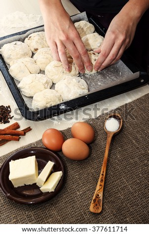 Easter concept. Ingredients for cooking easter pie. Hands placing raw dough ready for cooking on backing pan - stock photo