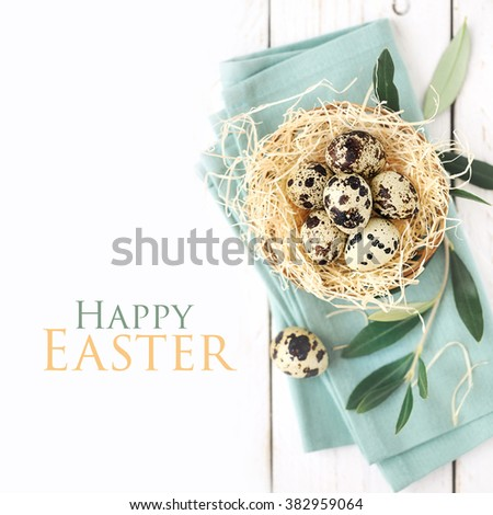 Easter concept - nest with quail eggs with an olive branch on a table napkin with Happy Easter greeting  - stock photo