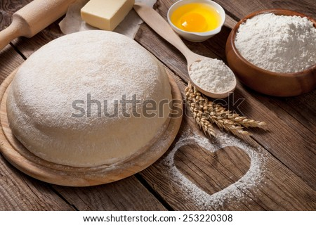 Easter concept. The dough is made from flour and heart on the table from the old boards - stock photo
