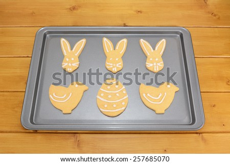 Easter cookies decorated with white frosting on a baking tray on a wooden table - stock photo