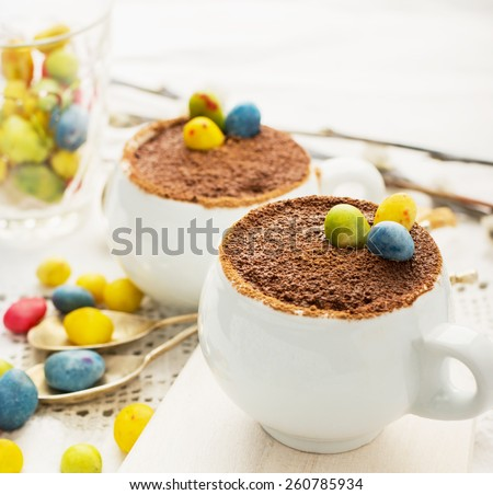 Easter cream dessert tiramisu based in portioned cups are decorated sweet candy in the form of eggs. Selective focus. - stock photo