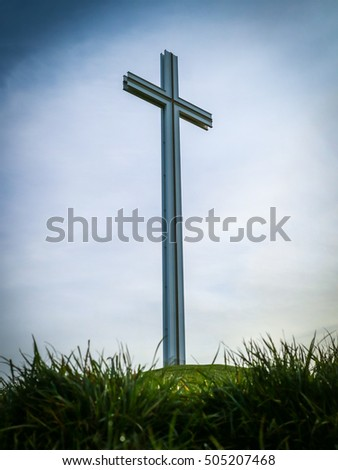 Easter cross with grass and blue sky